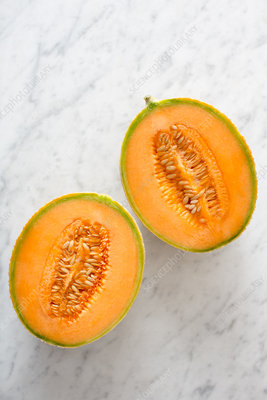 Two halves of cantaloupe melon on marble table