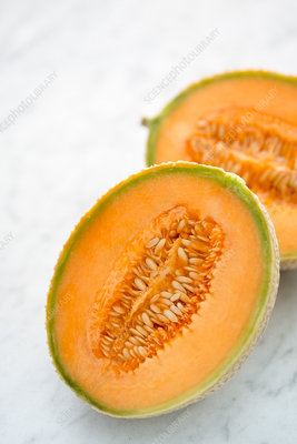 Two halves of cantaloupe melon on table