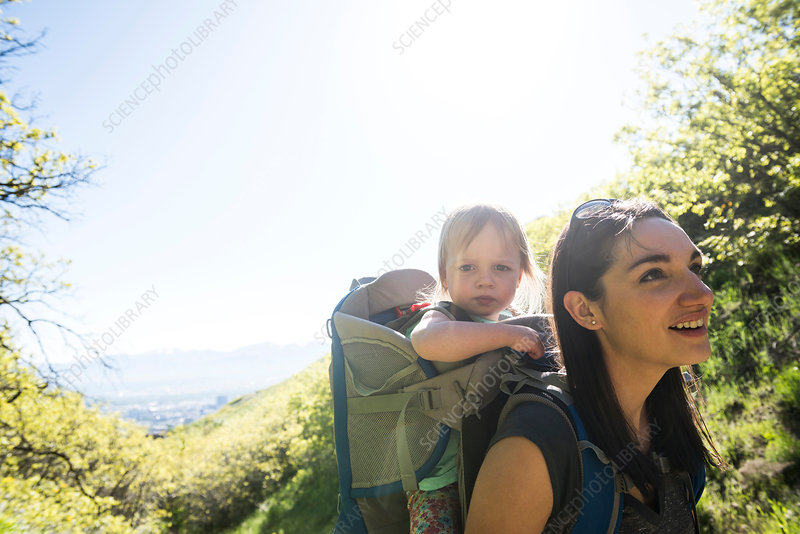 Mother carrying young daughter on back