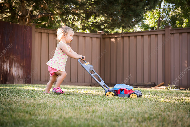 Young girl in garden, pushing toy lawn mower