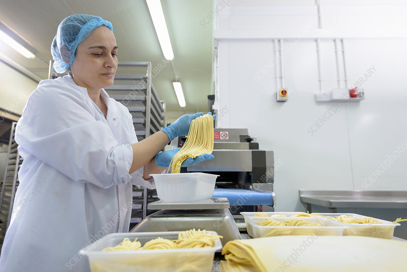 Female worker making tagliatelle in pasta factory