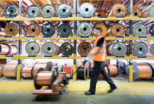 Worker with copper cable reels in cable factory