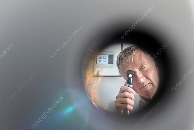 Optician looking into patient's eyes