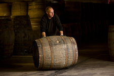 Worker rolling whisky cask in whisky distillery