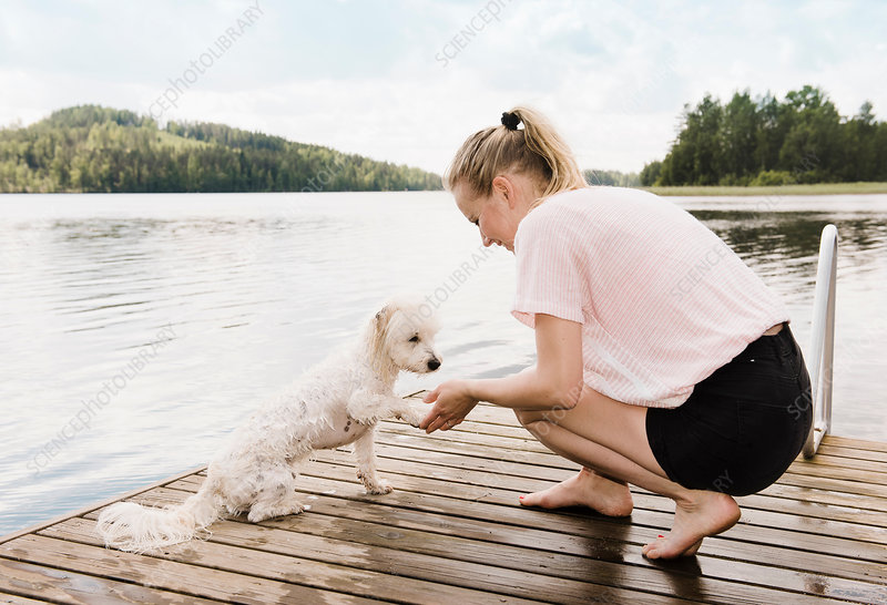 Woman holding dog's paw after swimming, Finland