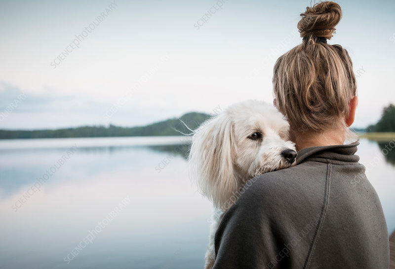 Dog looking over woman's shoulder at lake, Finland