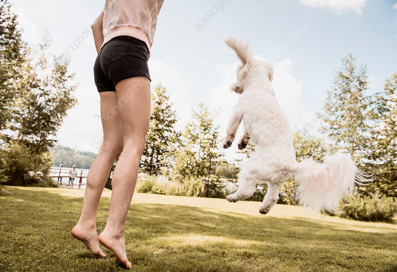 Woman jumping with dog in garden, Finland