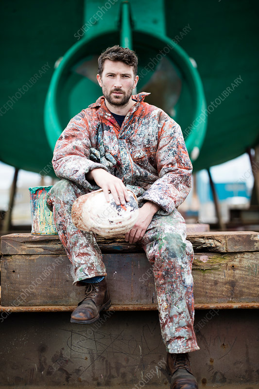 Male ship painter sitting in front of ship hull