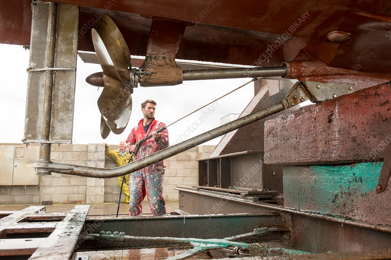 Male ship painter using pressure washer