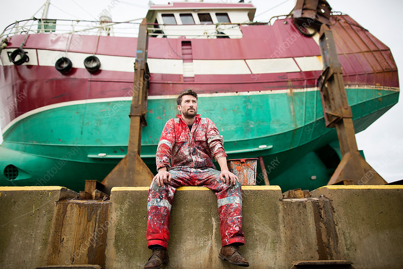 Male ship painter sitting in front of fishing boat