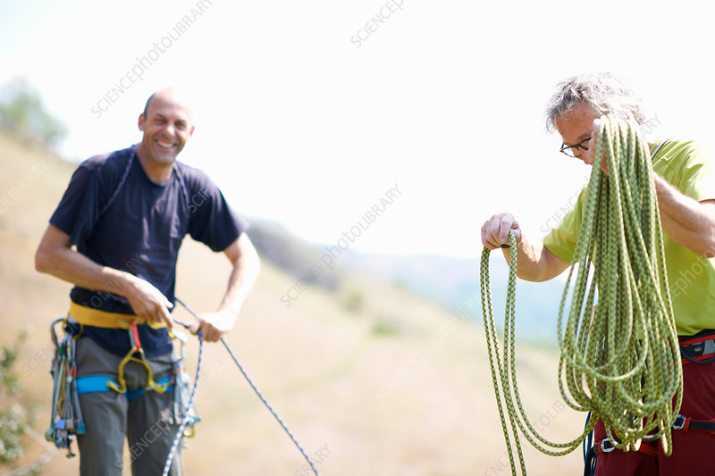 Rock climbers preparing rope smiling
