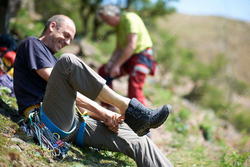 Man sitting on hillside putting on hiking boot
