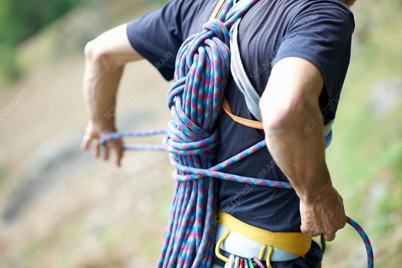 Rock climber carrying climbing rope on back