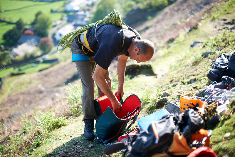 Rock climber on hillside preparing equipment