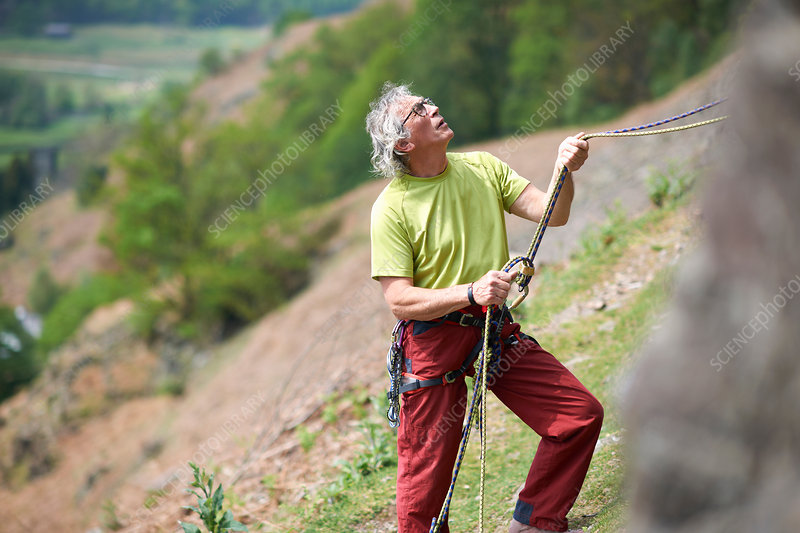 Rock climber holding climbing rope looking up