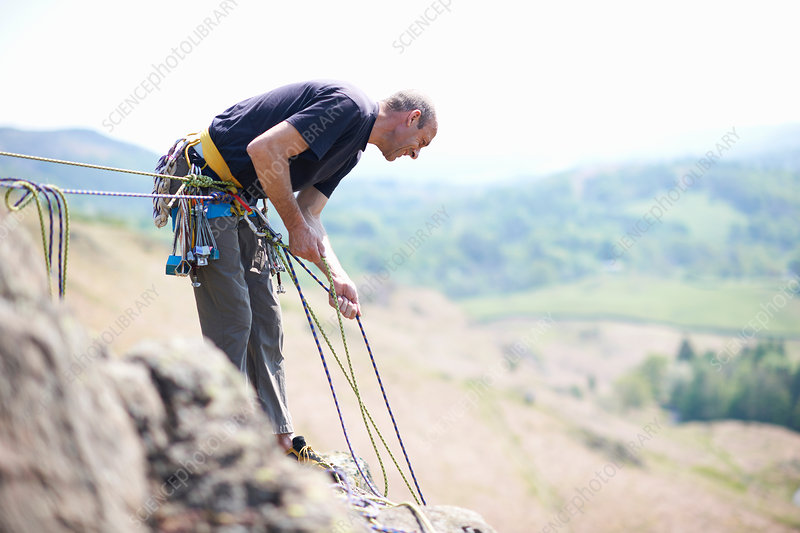 Rock climber holding climbing ropes looking down