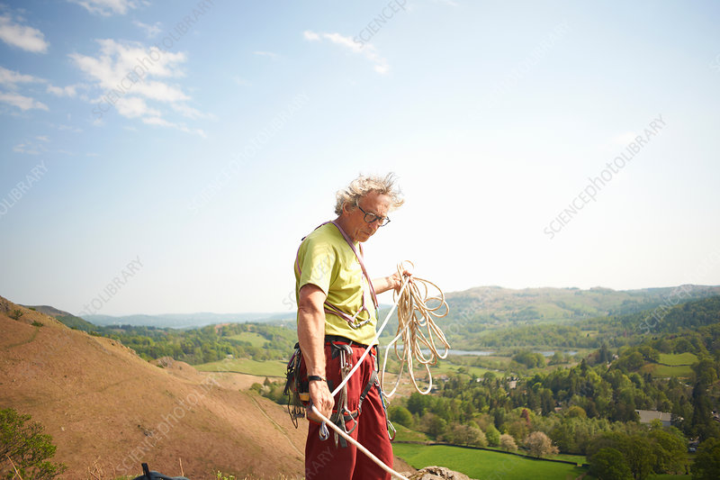 Rock climber on hillside preparing climbing rope