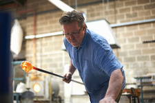 Glassblower in workshop holding blowpipe