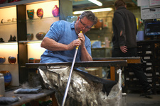Glassblower in workshop using blowpipe