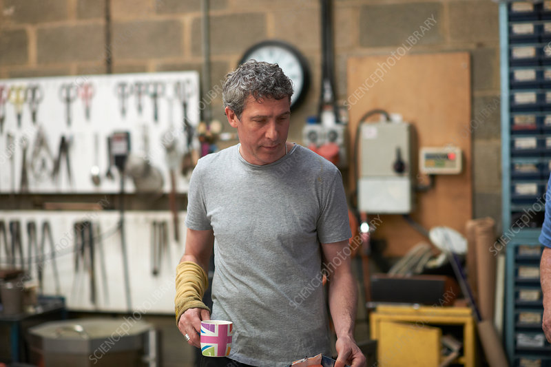 Glassblower in workshop holding mug