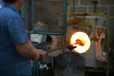 Glassblower in workshop using furnace