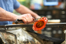 Glassblower in workshop shaping molten glass