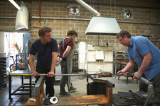Glassblowers in workshop using blowtorch