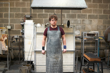 Glassblower in workshop wearing apron