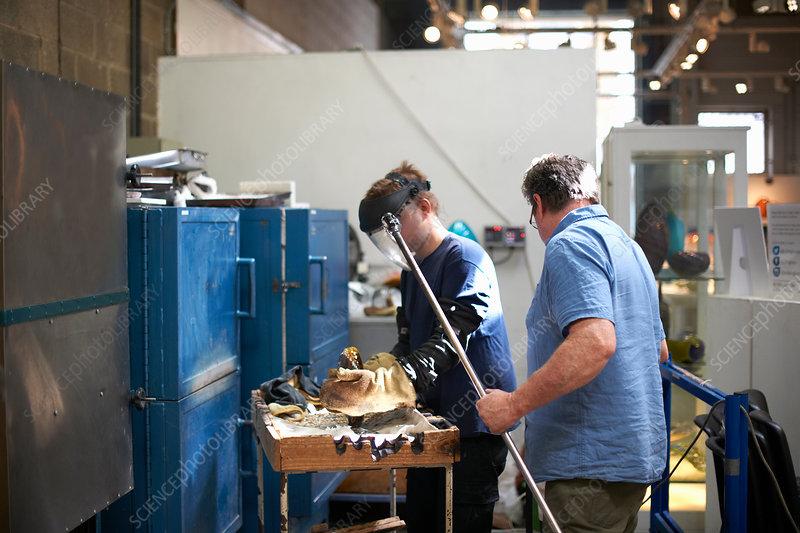 Glassblowers in workshop forming glass