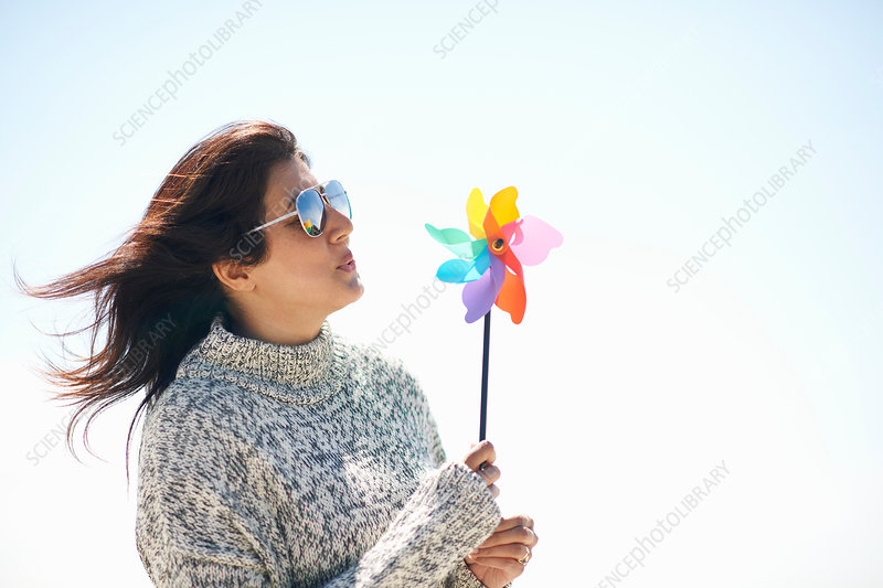 Woman wearing sunglasses holding pinwheel