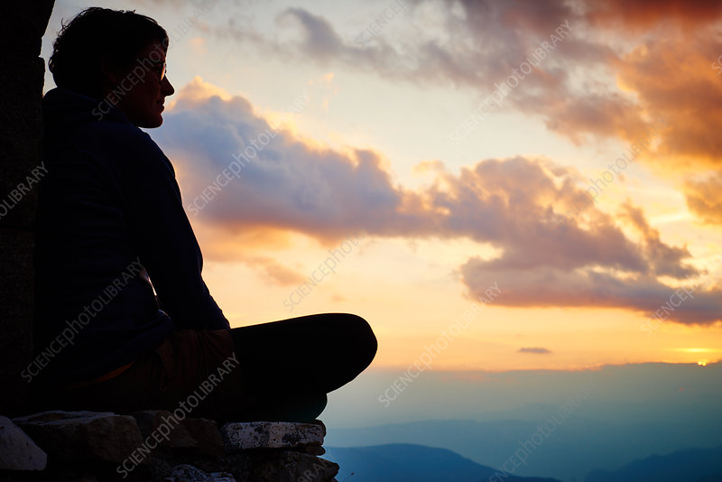 Woman sitting cross legged watching sunset