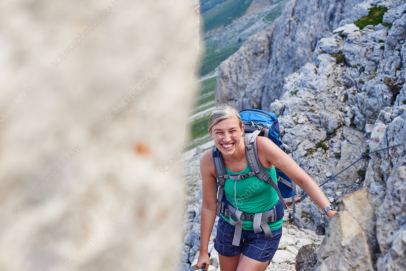 Woman hiking up mountain smiling