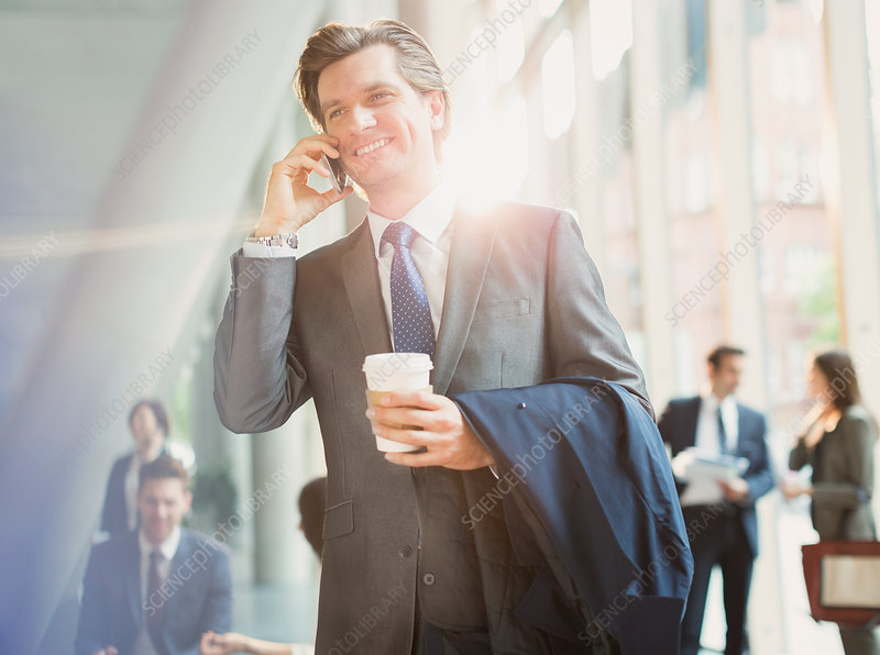 Businessman with coffee talking on cell phone