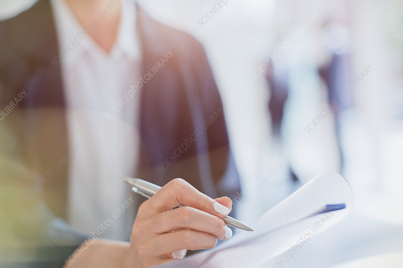 Close up businesswoman taking notes in meeting