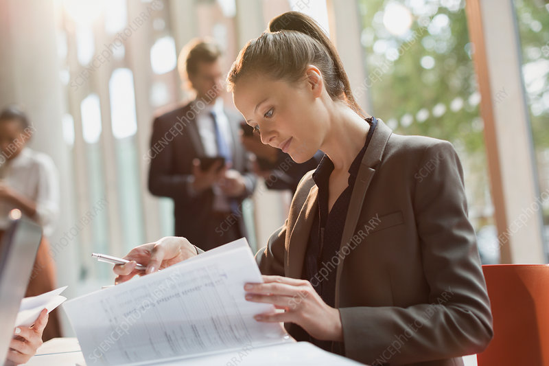 Businesswoman reading reviewing paperwork
