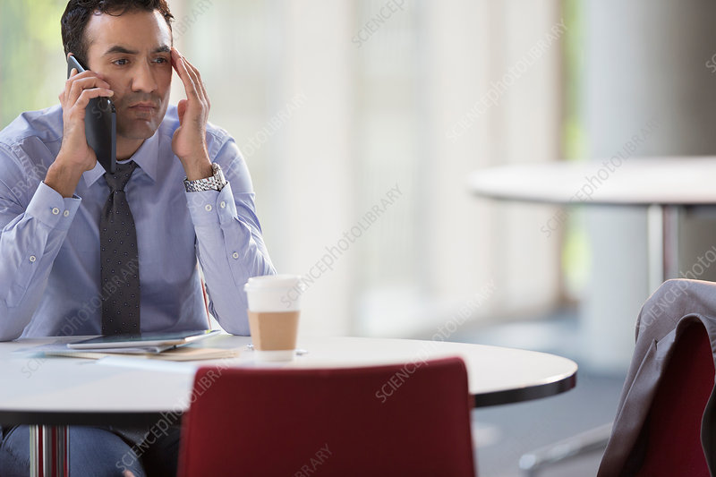 Stressed businessman talking on cell phone