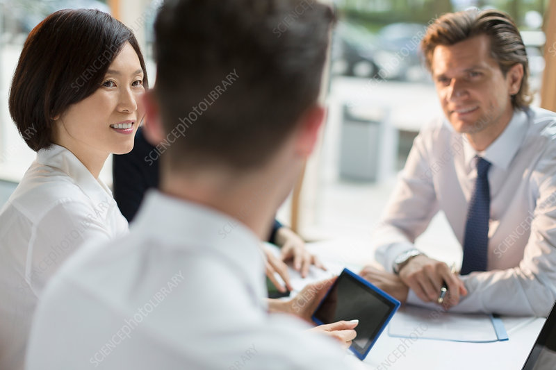 Business people with tablet talking in meeting