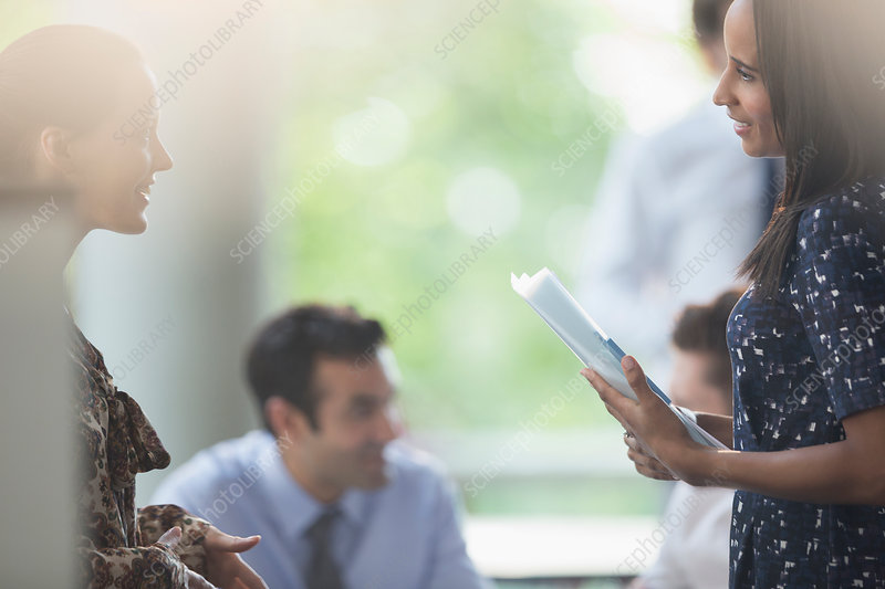 Businesswomen with paperwork talking in meeting