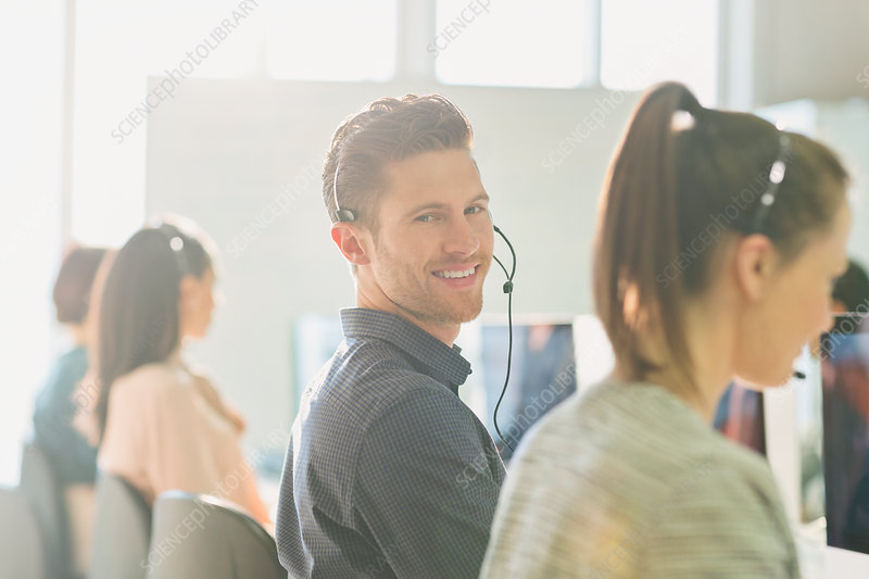 Male telemarketer wearing headset at computer