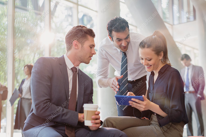 Business people with coffee using tablet, talking