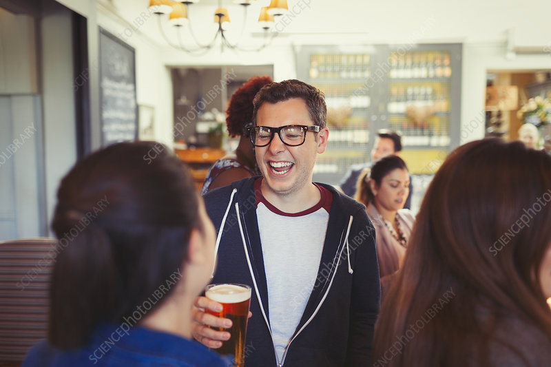 Man laughing and drinking beer with friends at bar