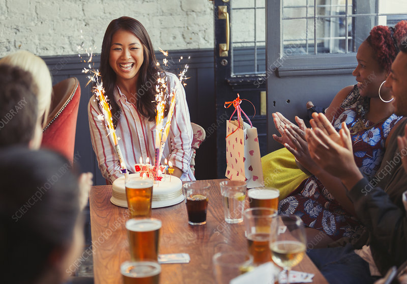 Friends clapping for woman with birthday cake