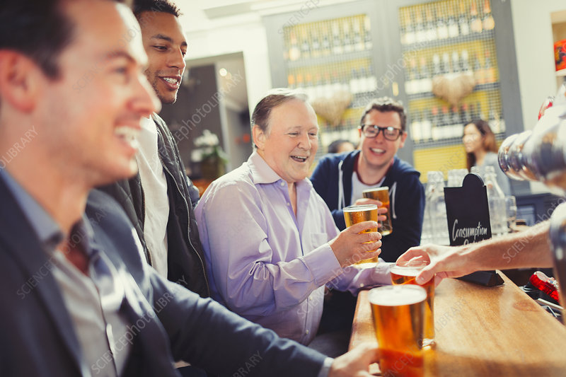Men friends drinking beer at bar