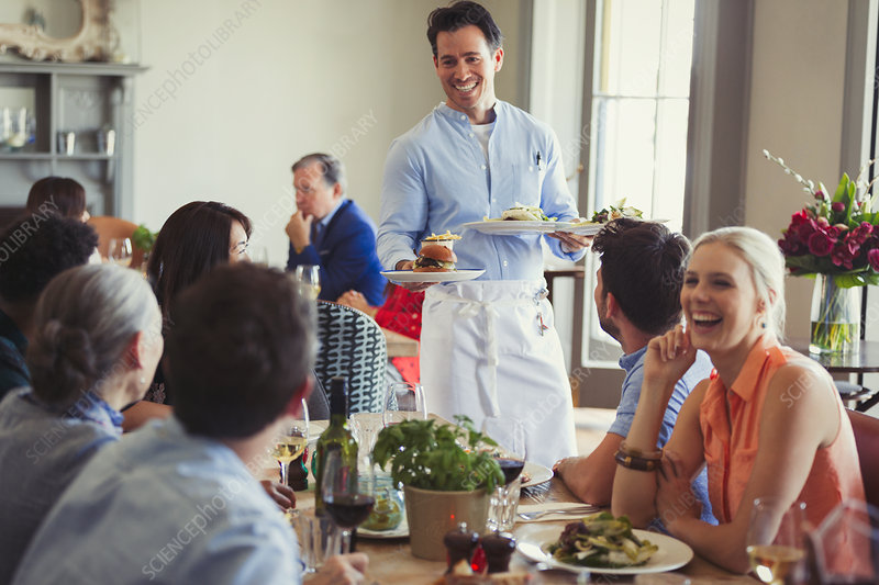Waiter serving food to friends dining