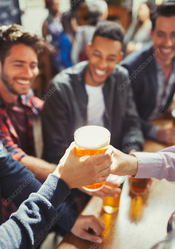 Waiter handing beer to man at bar