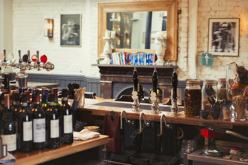 Wine bottles and tap handles behind bar