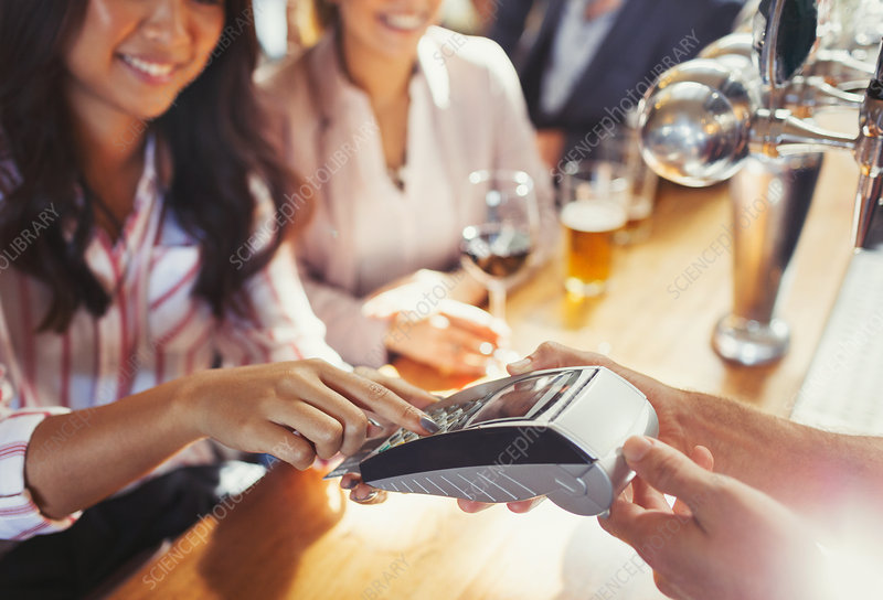 Woman paying bartender using credit card