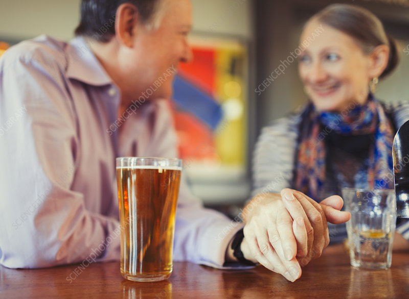 Senior couple holding hands drinking beer at bar