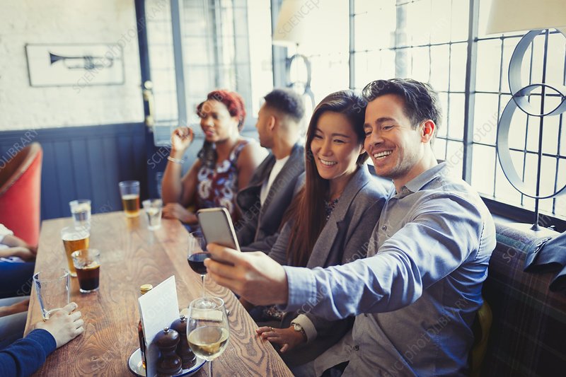 Smiling couple taking selfie with phone in bar