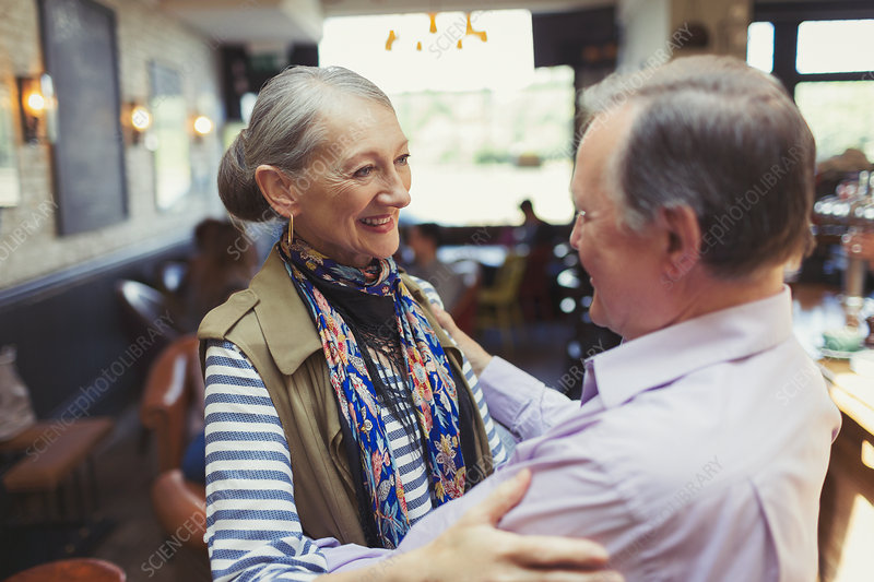 Affectionate senior couple hugging in bar